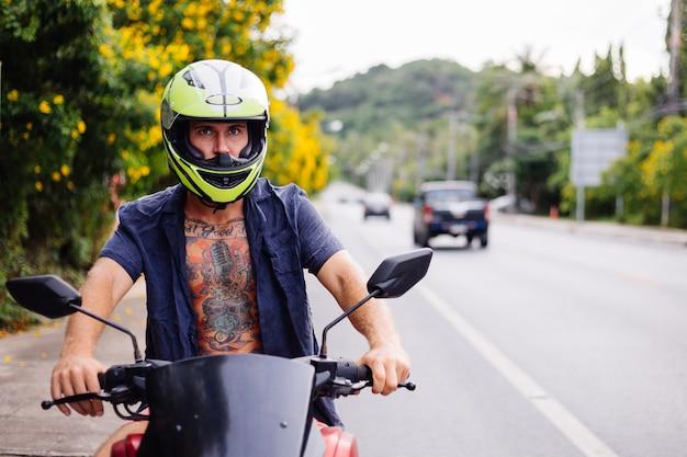Portrait of tattooed biker male in yellow helmet on motorbike on side of busy road in thailand