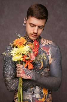 Portrait of a tattooed hipster man holding bouquet in hand against gray background