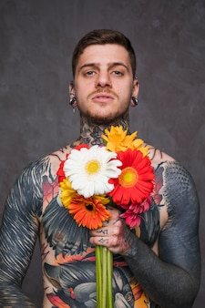 Portrait of a tattooed man with piercing in the ears and nose holding colorful gerbera flowers in hand