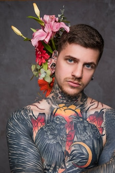 Portrait of a tattooed man with piercing in the ears and nose standing against grey backdrop