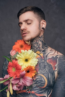 Portrait of a tattooed young man with flowers on his shoulder and piercer ears against grey background