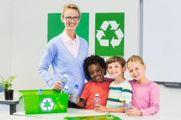 Portrait of teacher and kids standing in classroom