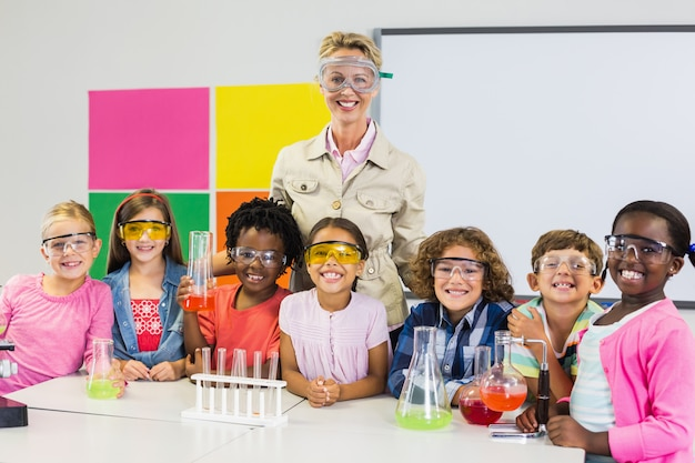 Portrait of teacher and kids standing in laboratory