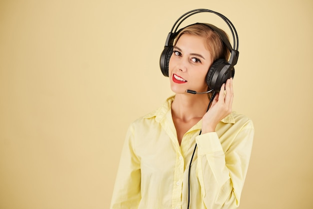 Portrait of technical support operator in headset having problems with connection, isolated on light yellow