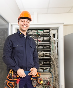 Portrait of a technician in front of a network rack