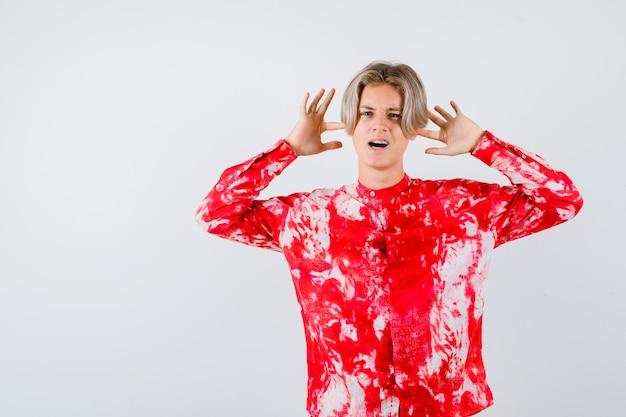 Ritratto di adolescente maschio biondo che mostra gesto di resa in camicia oversize e guardando vista frontale turbata