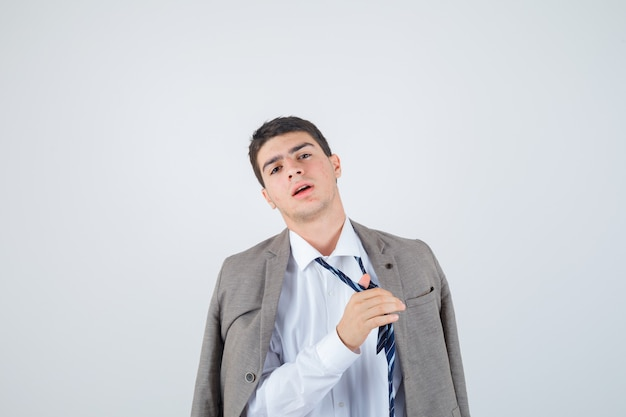 Portrait of teen boy loosen tie while posing in shirt, jacket, striped tie and looking fatigued front view