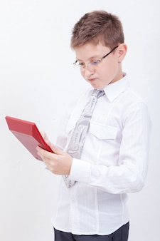 Portrait of teen boy with calculator over white background