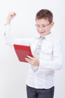 Portrait of teen boy with calculator on white wall
