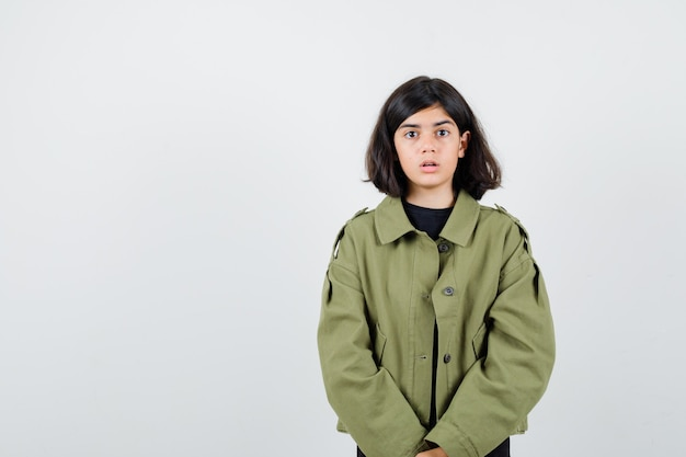 Portrait of teen girl in army green jacket and looking puzzled front view