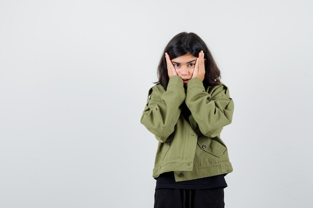 Portrait of teen girl holding hands on cheeks in army green jacket and looking forgetful front view
