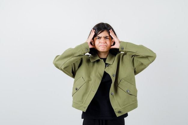 Portrait of teen girl holding hands near face in army green jacket and looking wistful front view