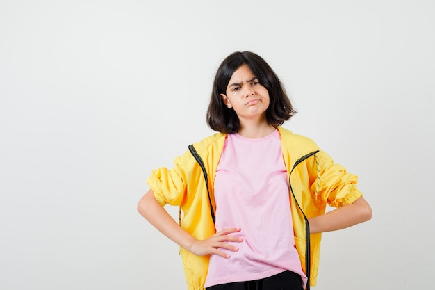 Portrait of teen girl keeping hand behind back while posing in t-shirt, jacket and looking sad front view