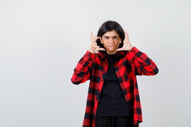 Ritratto di una ragazza adolescente che tiene le mani vicino al viso in camicia casual e sembra una vista frontale aggressiva