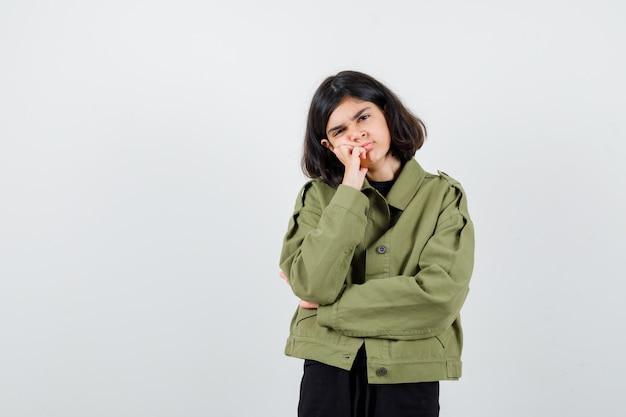 Ritratto di una ragazza adolescente appoggiata sulla guancia con una giacca verde militare e dall'aspetto triste vista frontale