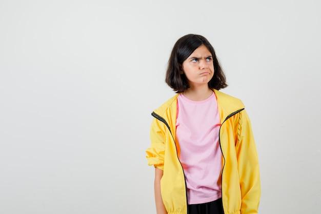 Ritratto di ragazza adolescente che guarda lontano in t-shirt, giacca e sembra sconvolta vista frontale
