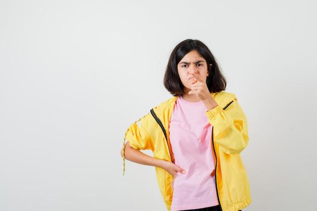 Ritratto di una ragazza adolescente che punta via in maglietta, giacca e sembra sconvolta vista frontale