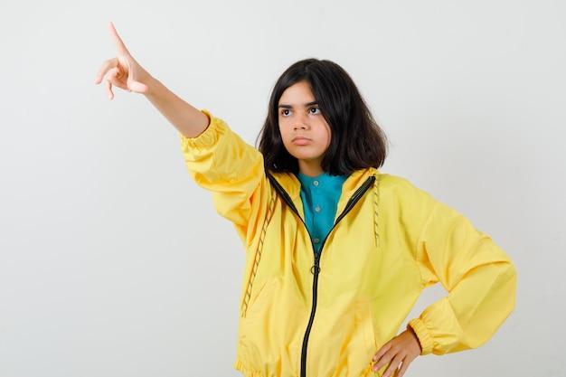 Ritratto di una ragazza adolescente che punta via in giacca gialla e guarda una vista frontale cupa