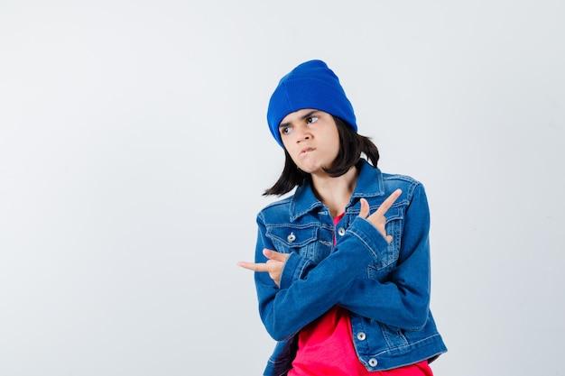 Ritratto di ragazza adolescente che punta a destra ea sinistra in giacca di jeans, berretto e guardando la vista frontale focalizzata