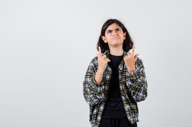 Ritratto di una ragazza adolescente rivolta verso l'alto, guardando in alto in camicia casual e guardando la vista frontale esitante