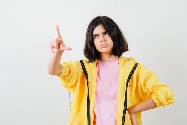 Ritratto di una ragazza adolescente che punta verso l'alto in maglietta, giacca e guarda seria vista frontale