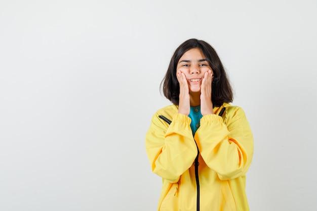 Ritratto di una ragazza adolescente che finge di strofinare la crema per la pelle sulle guance in giacca gialla e guarda con attenzione la vista frontale
