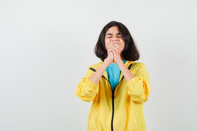 Ritratto di una ragazza adolescente che mostra le mani giunte in un gesto implorante in giacca gialla e guarda una vista frontale speranzosa