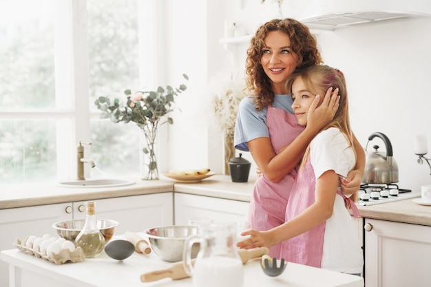 Portrait of a teen girl with her mother at home in kitchen