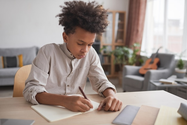 Portrait of teenage african-american boy doing homework and writing in notebook while sitting at desk in home interior, copy space