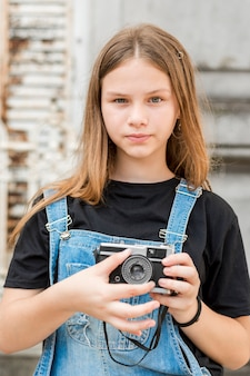 Portrait of teenage beautiful girl holding retro camera