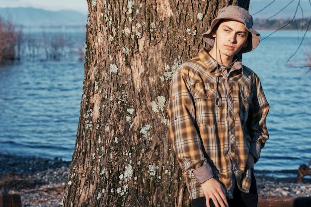 Portrait of a teenage boy in boy scout clothes posing under a tree near a lake