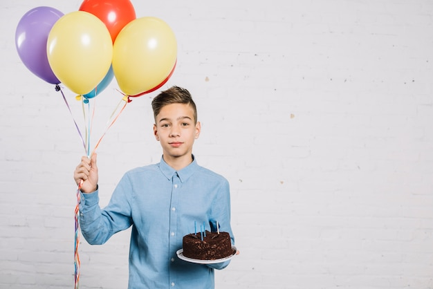 Portrait of teenage boy holding balloons and birthday cake against wall