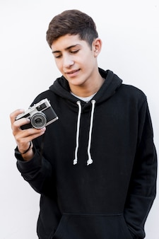 Portrait of a teenage boy looking at vintage camera standing against white background