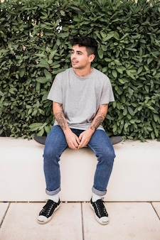 Portrait of a teenage boy sitting on skateboard