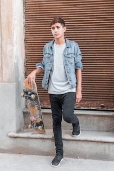 Portrait of teenage boy standing in front of closed corrugated iron siding holding skateboard