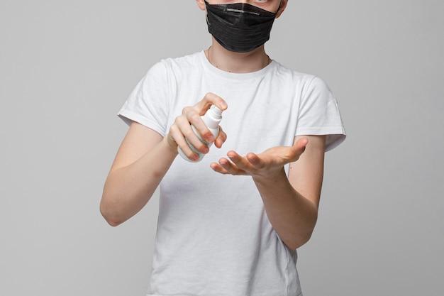 Portrait of teenage boy stands in black medical mask