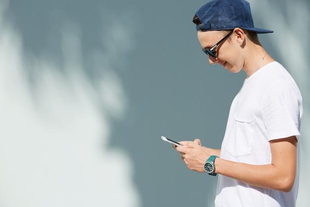Ritratto di adolescente con occhiali da sole e berretto