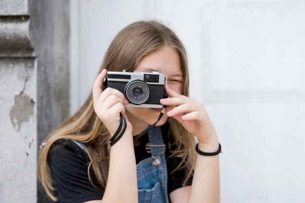 Portrait of a teenage female photographer covering her face with the camera