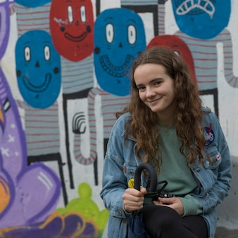 Portrait of teenage girl sitting in front of graffiti covered wall, florentin, tel aviv, israel