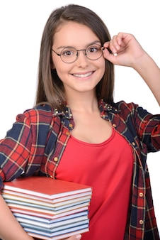 Portrait of teenage girl with glasses holding books.