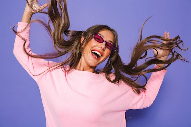 Portrait of teenage girl with two ponytails in sweatshirt wearing trendy sunglasses and playing with her hair
