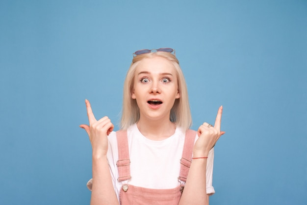 Portrait teenage with light hair with astonishment and shows fingers up on the ad.