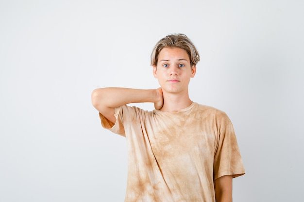 Portrait of teenager boy keeping hand on neck in t-shirt and looking troubled front view