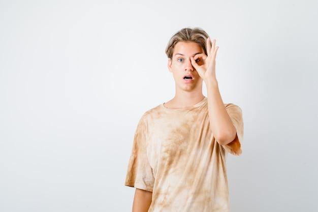 Ritratto di un ragazzo adolescente che mostra il segno ok sull'occhio in maglietta e sembra una vista frontale scioccata