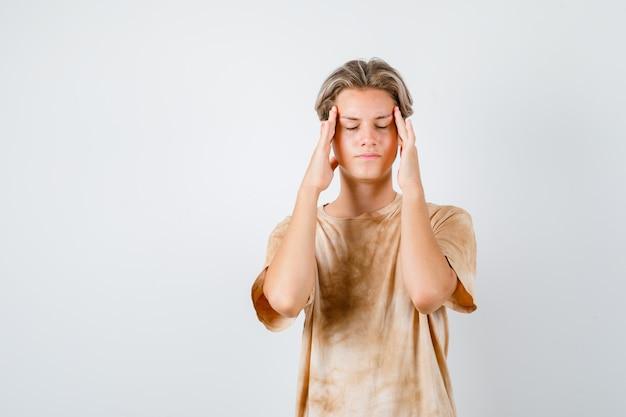 Ritratto di un ragazzo adolescente che soffre di emicrania in maglietta e che sembra esausto vista frontale