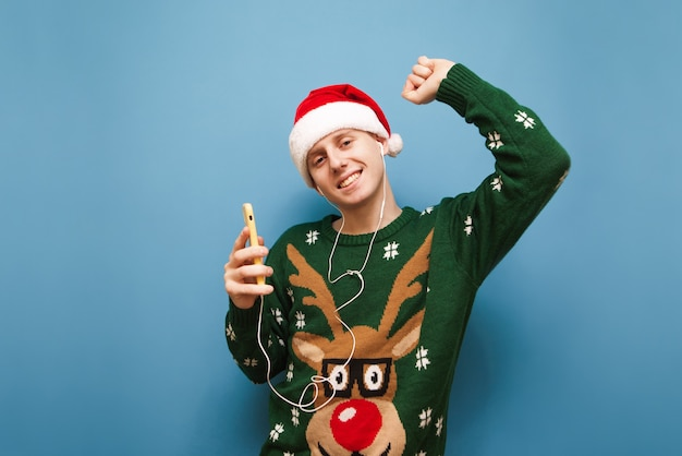 音楽を聞いているクリスマスセーターと肖像画のティーンエイジャーの少年