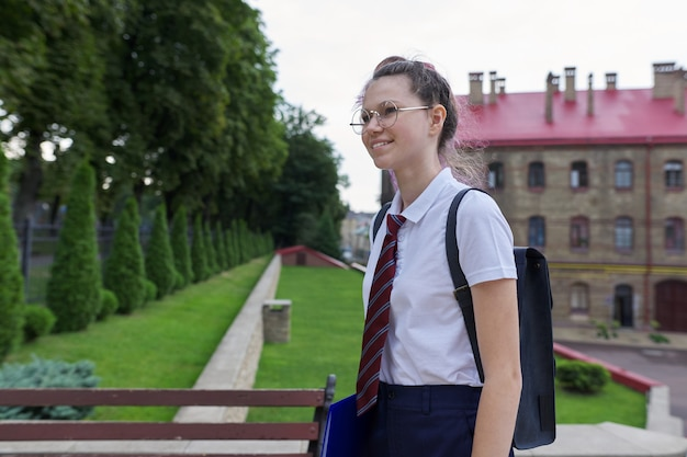 Portrait of teenager girl with backpack going to school, summer autumn morning, school building background. back to school, back to college
