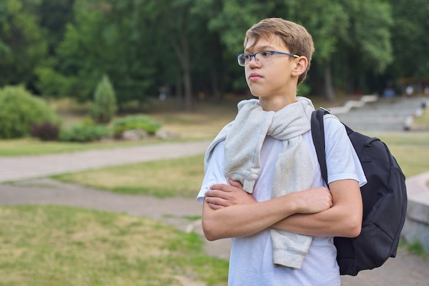 Portrait of teenager schoolboy in glasses with backpack