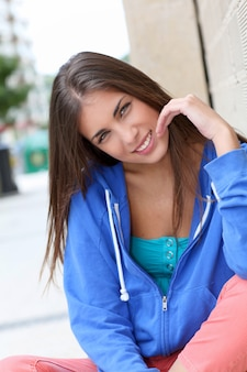 Portrait of teenager sitting in the street