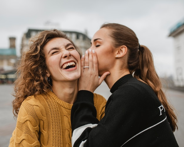 Ritratto di un adolescente che bisbiglia all'orecchio dei suoi amici